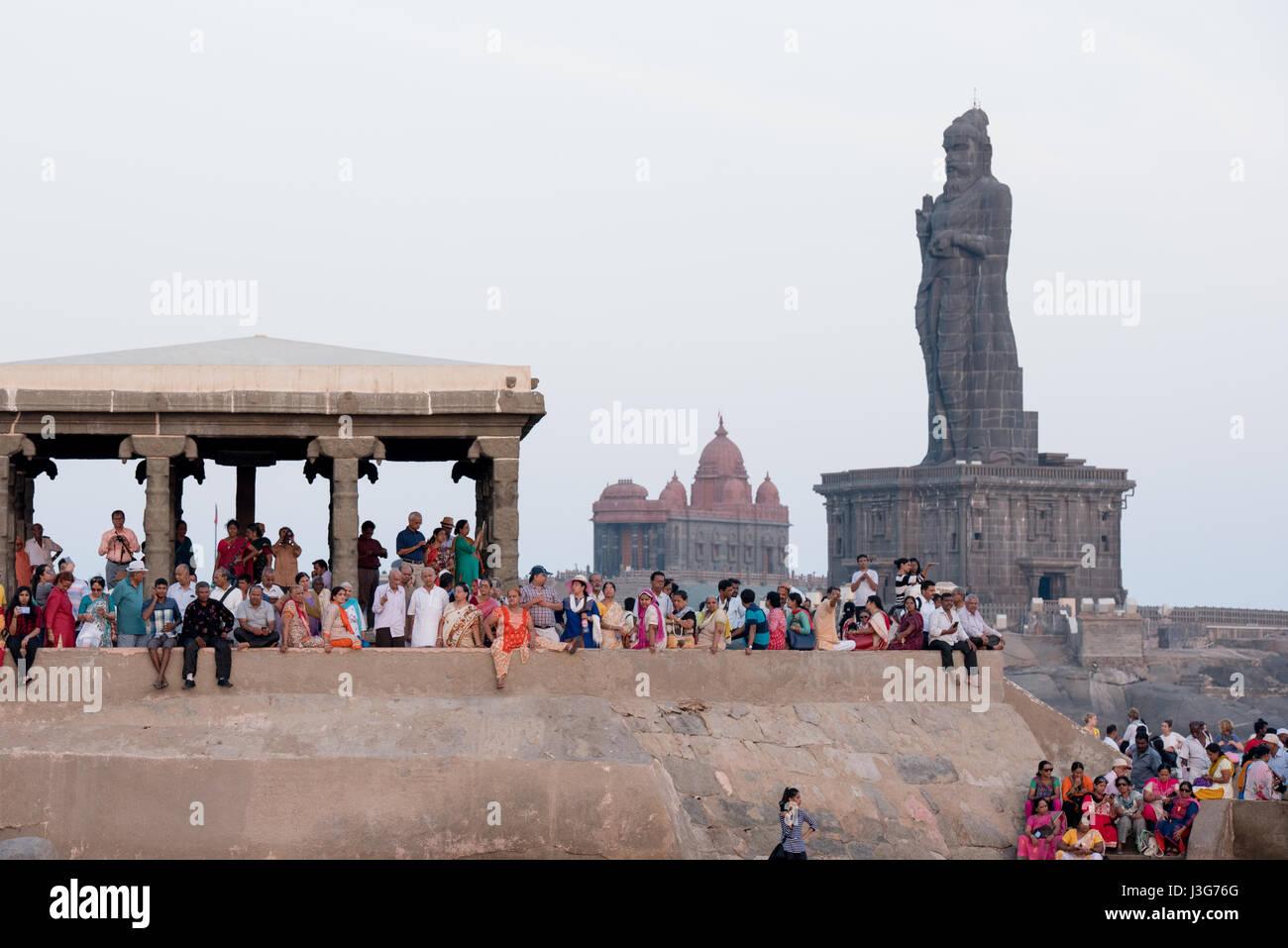 Una folla di gente che godersi il tramonto di fronte alla statua di Thiruvalluvar in Kanyakumari, India Immagini Stock