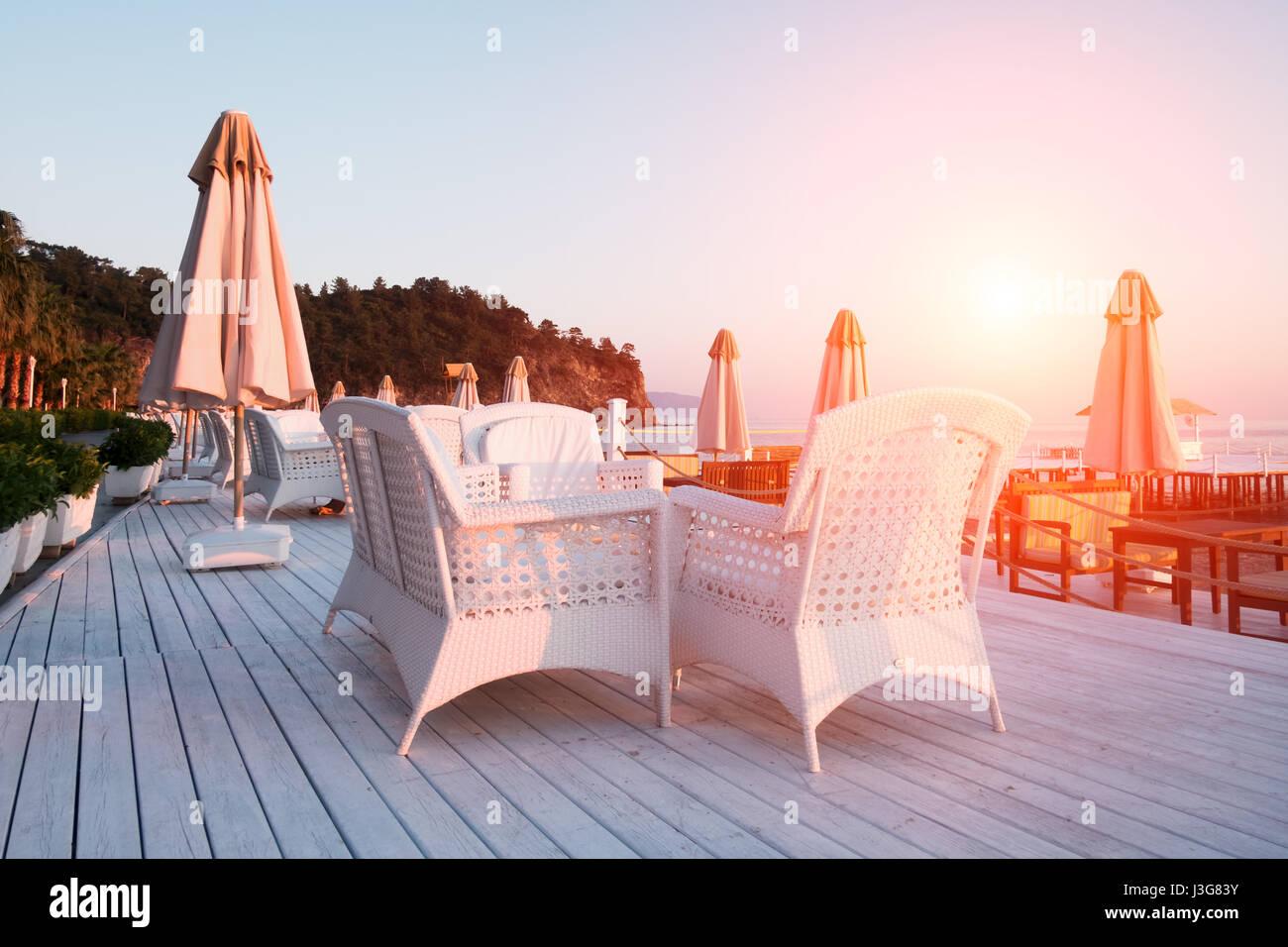 Ristorante estivo sulla spiaggia. Vista mozzafiato sul mar Mediterraneo. Bianco terrazzo in legno e arredo intrecciato Immagini Stock