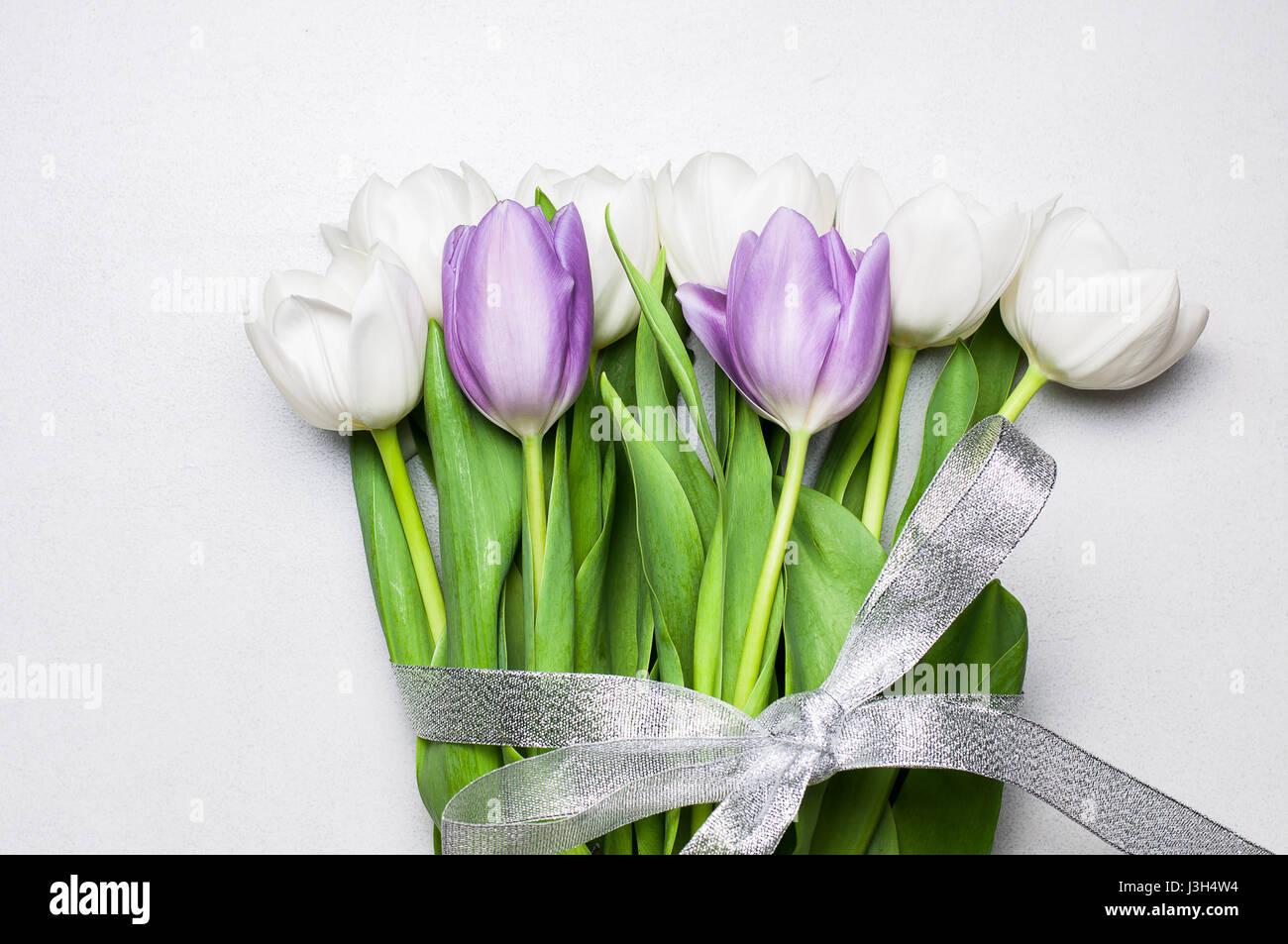 Bouquet di bianco e viola i tulipani con nastro argentato su un