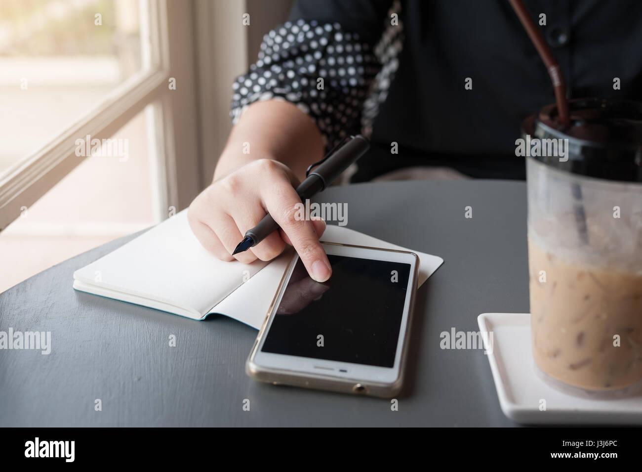 Donna mano toccando lo schermo dello smartphone durante la scrittura di qualcosa nel coffee shop. Lavorare da qualsiasi Immagini Stock