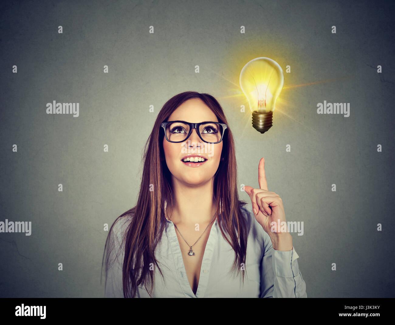 Ritratto di donna puntando alla luce brillante lampadina. Il successo crescente il concetto di business Immagini Stock