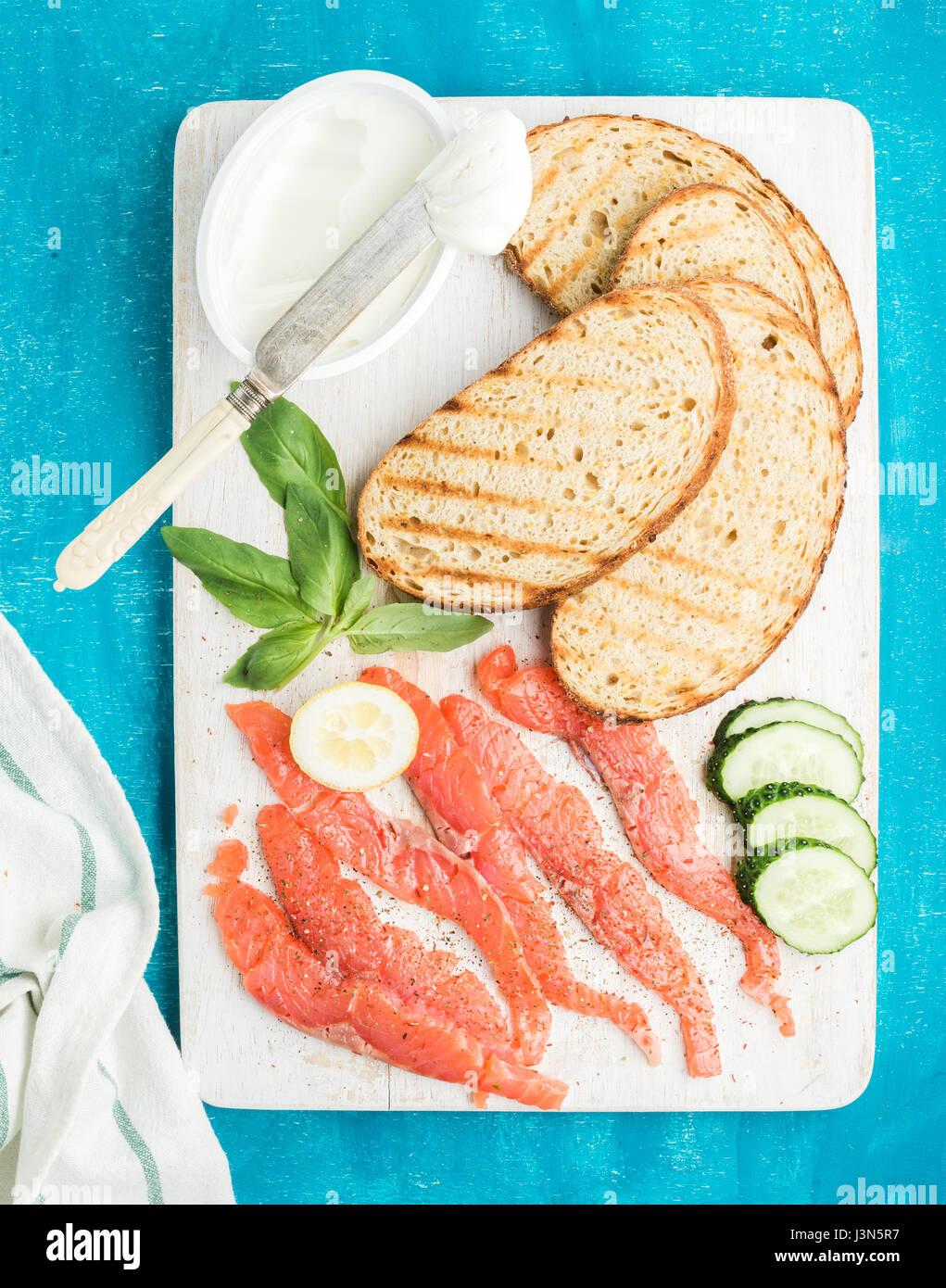 Ingredienti per una sana sandwich. Grigliate le fette di pane, salmone affumicato, ricotta, cetriolo e basilico Immagini Stock