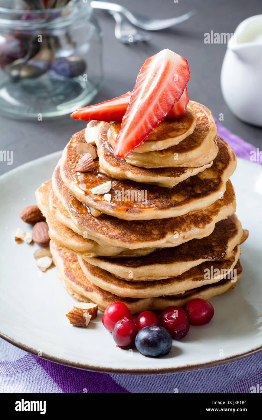 Pila di pancake con frutta fresca e miele. Primo piano verticale foto di cibo Immagini Stock