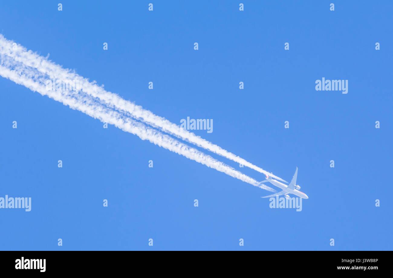 Contrails da un getto aereo contro il cielo blu. Immagini Stock