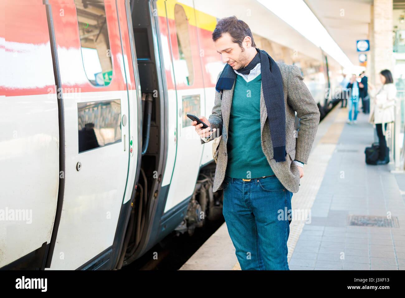 Uomo in piedi in attesa per il treno in una stazione ferroviaria platform Immagini Stock