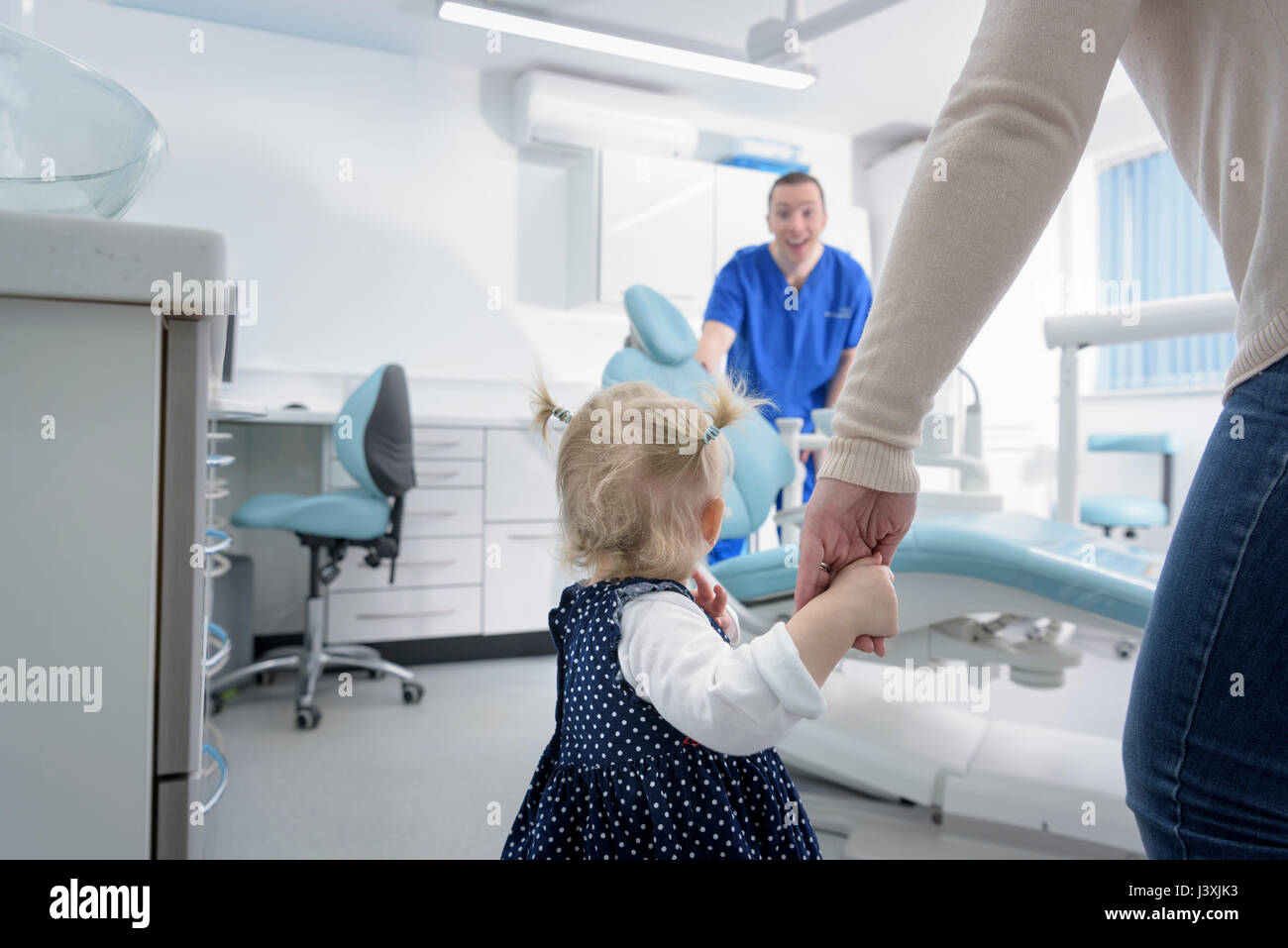 Bambina entrando in chirurgia dentale con la madre Immagini Stock