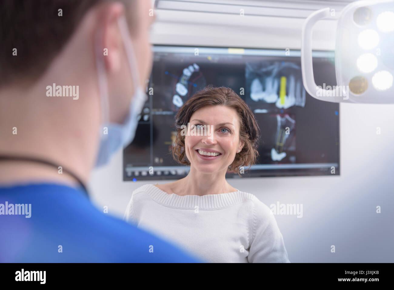 Dentista che mostra i raggi x sullo schermo al paziente in chirurgia dentale Foto Stock