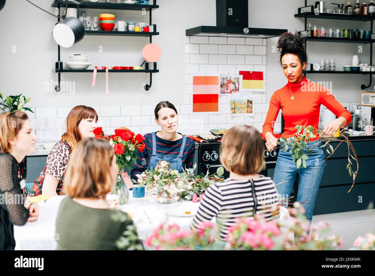 Fioraio insegnando agli studenti in fiore organizzando workshop Immagini Stock