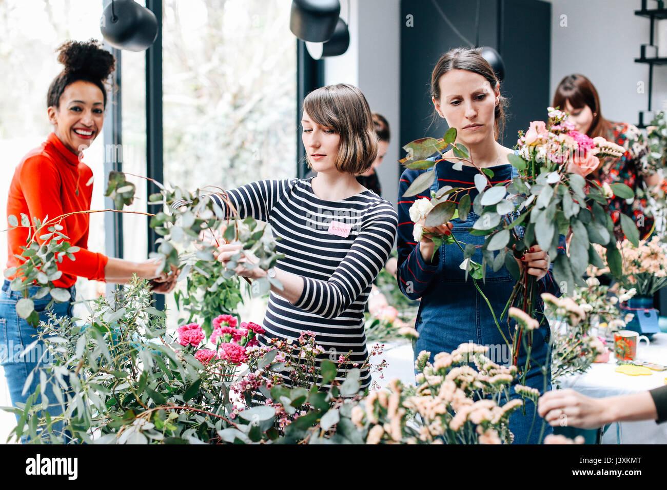Fioraio studenti selezionando i fiori recisi a decorazione floreale workshop Immagini Stock