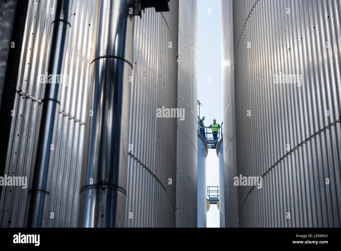 Lavoratore sulla parte superiore dei serbatoi di stoccaggio dell'olio in fabbrica di miscelazione Immagini Stock
