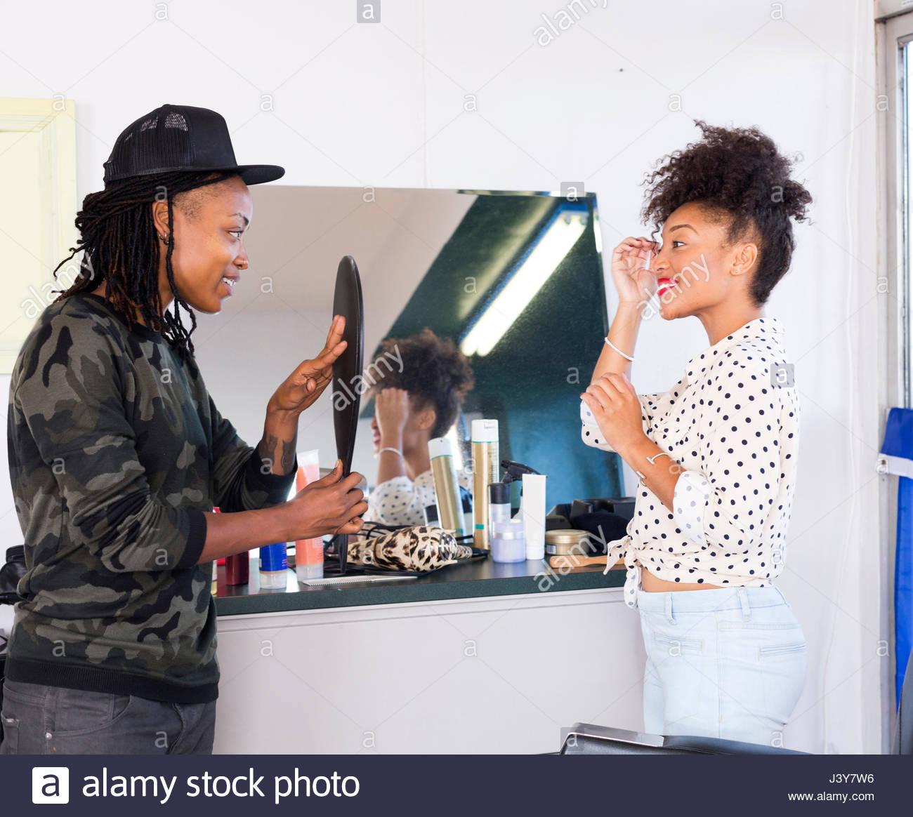 Barbiere femmina tenendo la mano specchio per il cliente in un barbiere Immagini Stock
