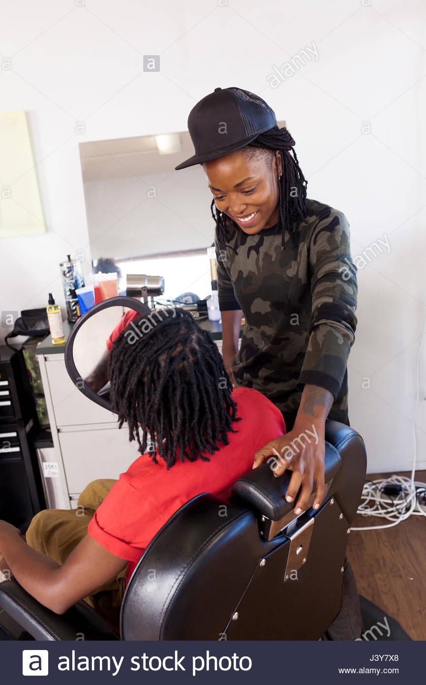 Barbiere femmina tenendo la mano specchio per il cliente in un barbiere Foto Stock