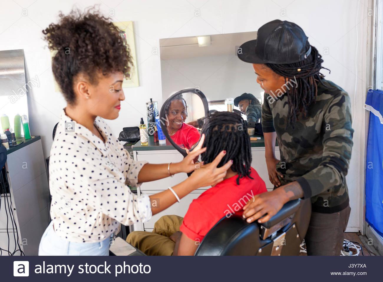 I clienti che cercano in mano specchio in un barbiere Immagini Stock