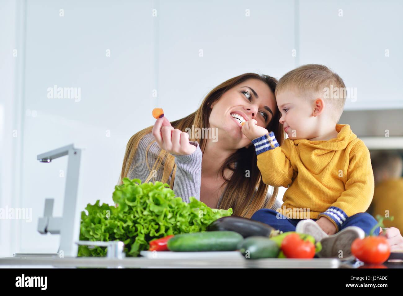 La madre e il bambino a preparare il pranzo da verdure fresche Immagini Stock