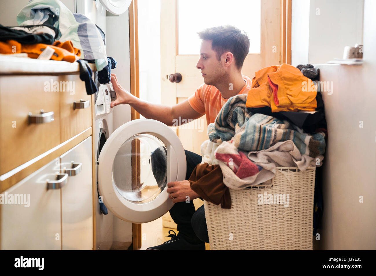 Uomo che fa servizio lavanderia a casa Immagini Stock