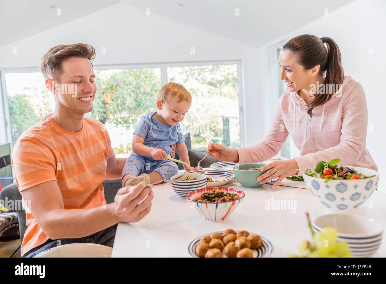 Giovane famiglia avente la colazione nella cucina di casa Immagini Stock