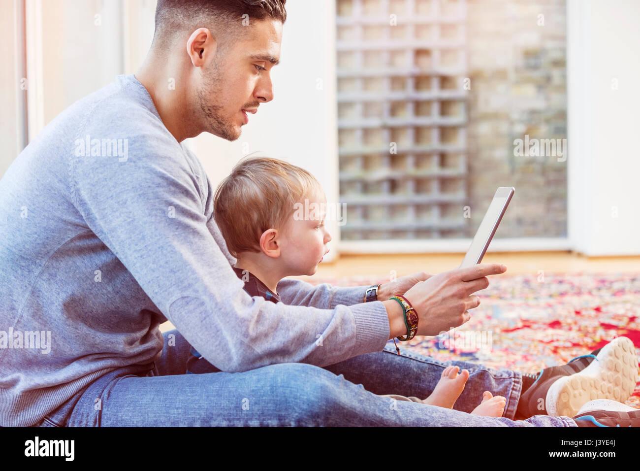 Padre e figlio toddler sedersi sul pavimento di casa utilizzando tablet Immagini Stock