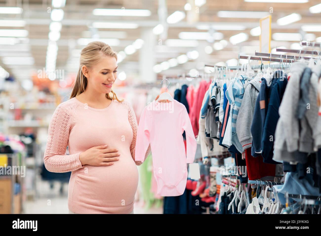 Donna incinta con vestiti del bambino al negozio di abbigliamento Immagini  Stock 09dccf3c09d