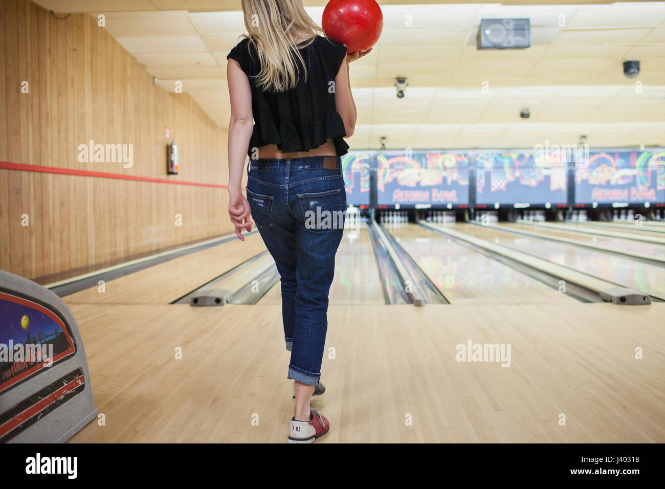 Una giovane donna bowling. Immagini Stock