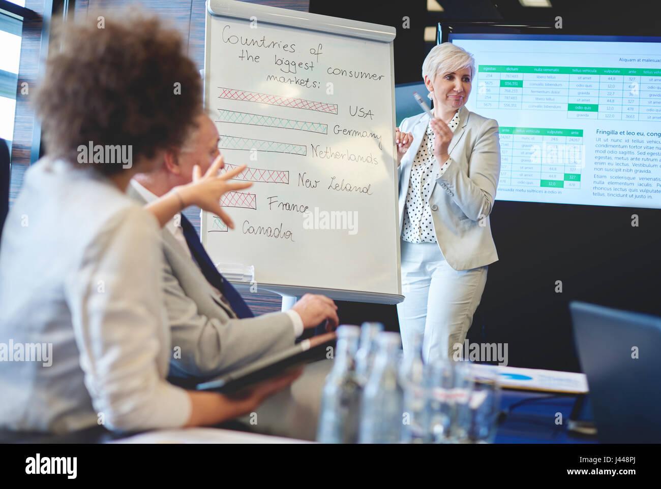 Leader femmina utilizzando apparecchiature aziendali Immagini Stock