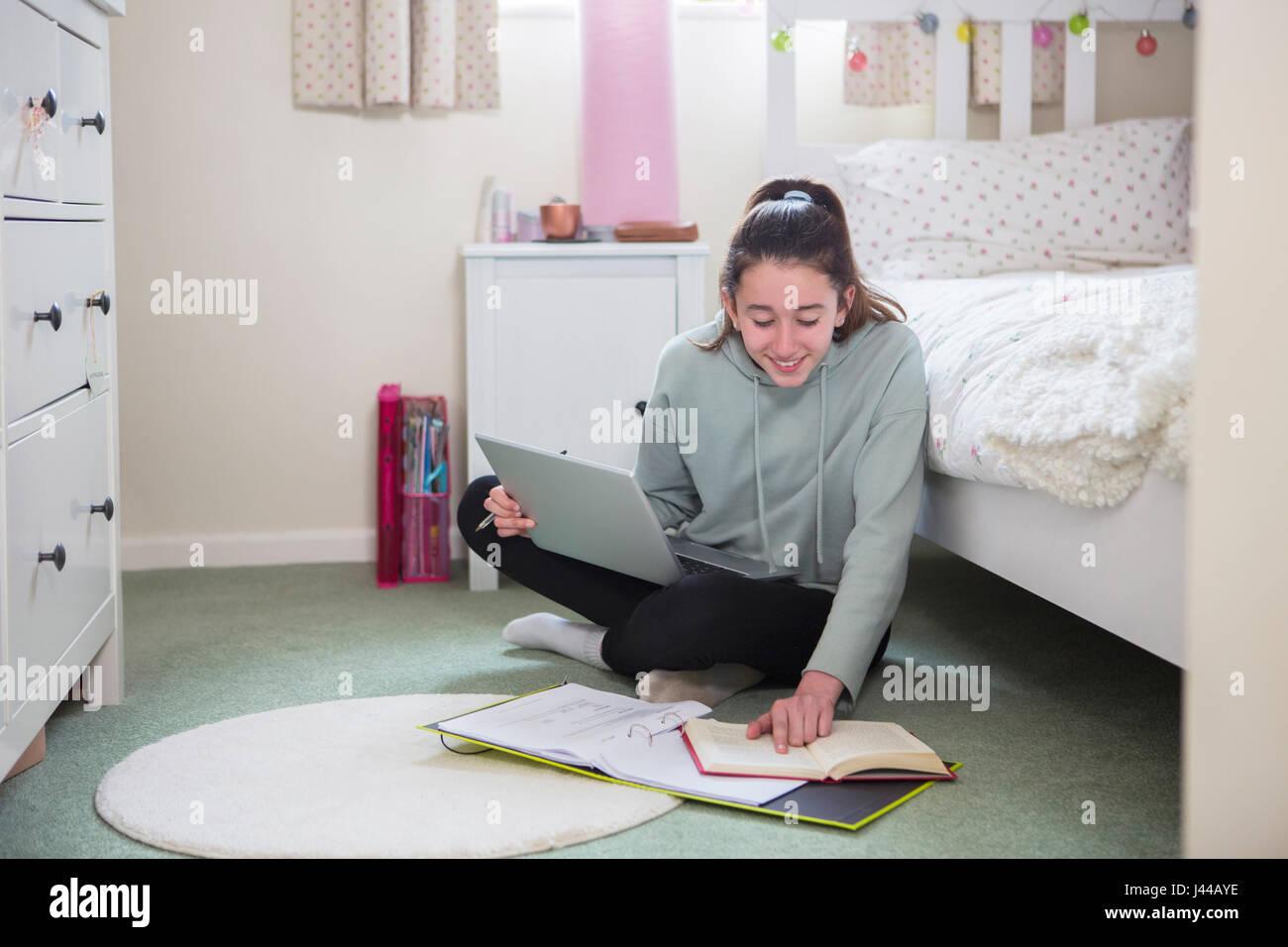 Giovane ragazza seduta sul pavimento della camera da letto facendo i compiti sul computer portatile Immagini Stock