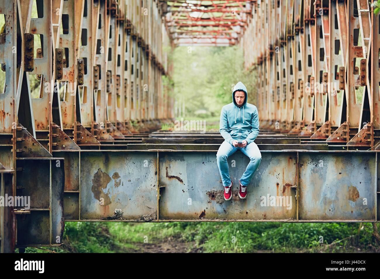 Triste Uomo con telefono cellulare sul abbandonato ponte arrugginito. Concetto di tristezza e solitudine, collegamento Foto Stock