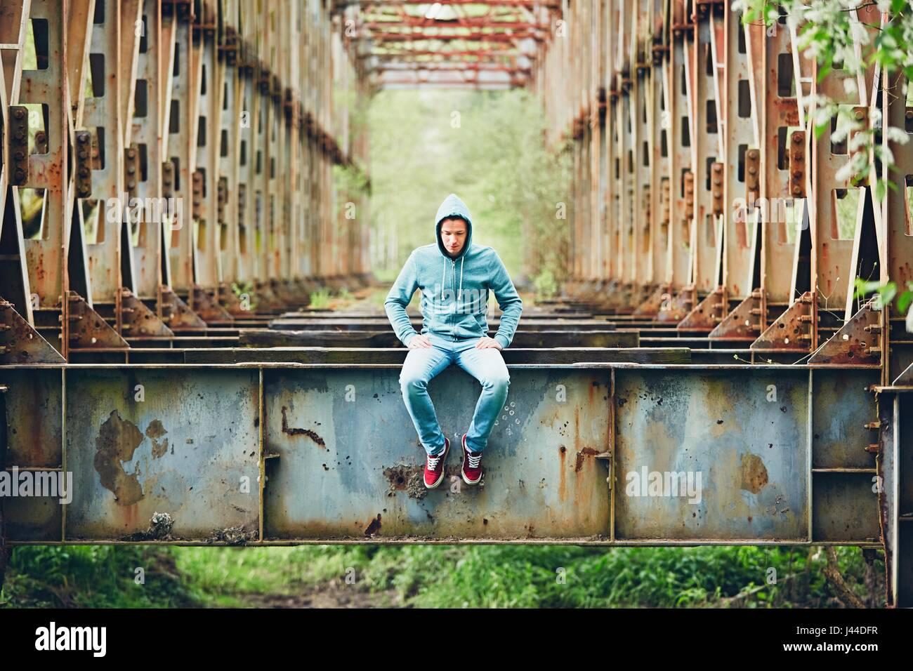 Triste uomo seduto sull'abbandonato ponte arrugginito. Concetto di tristezza e di solitudine e di più. Immagini Stock