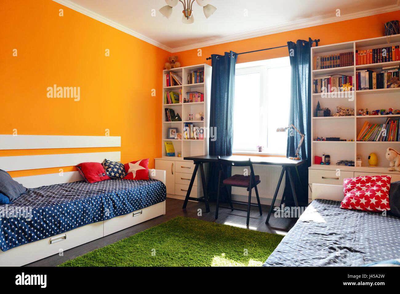 Camera da letto per bambini in arancione e blu con due letti e ...