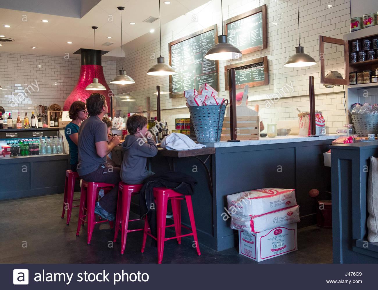Persone sedute su sgabelli a contatore interno locale pizza