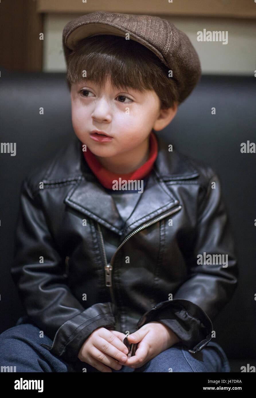 Po  di razza mista asian caucasian boy con capelli castani indossando una  pelle nera rockabilly motocicletta giacca marrone con newsboy cap ce37205dc03f