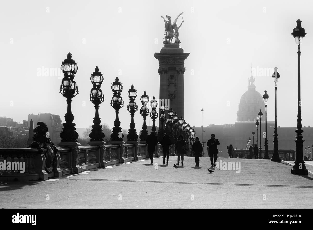 La gente cammina sullo storico ponte Alexandre III ( Pont Alexandre III ) a Parigi. Immagine in bianco e nero. Immagini Stock