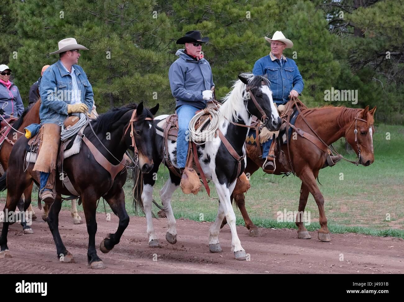 Stati Uniti Il Segretario degli Interni Ryan Zinke, centro, prende un cavallo con allevatori locali durante un tour Foto Stock