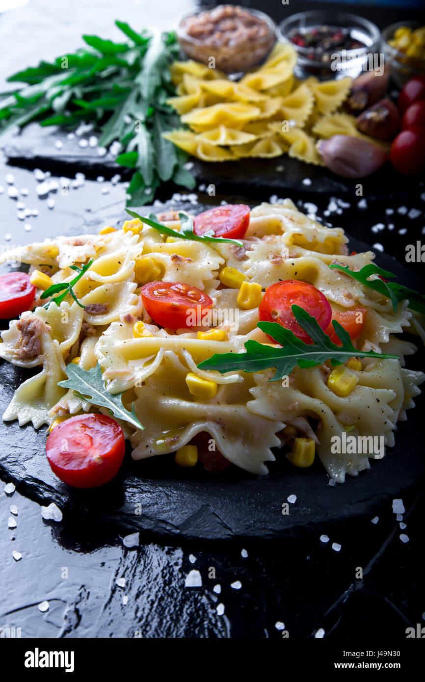 Insalata di pasta nella piastra di ardesia con pomodori ciliegia, tonno, mais e foglie di rucola. ingredienti. Il Immagini Stock