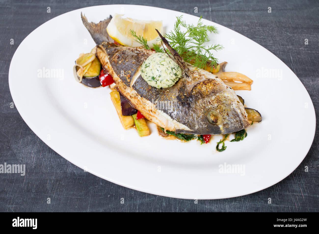Dorado cotto con il burro e le verdure. Piastra situata su una tavola nera come sfondo. Foto Stock