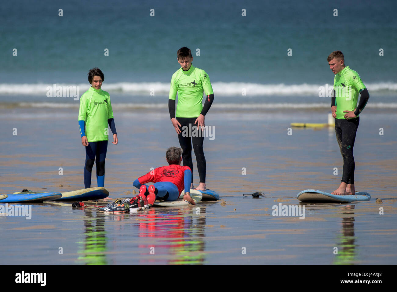 Una scuola di surf istruttore insegnamento novizi Newquay Cornwall Surf Surfer ai partecipanti imparare Coaching Immagini Stock
