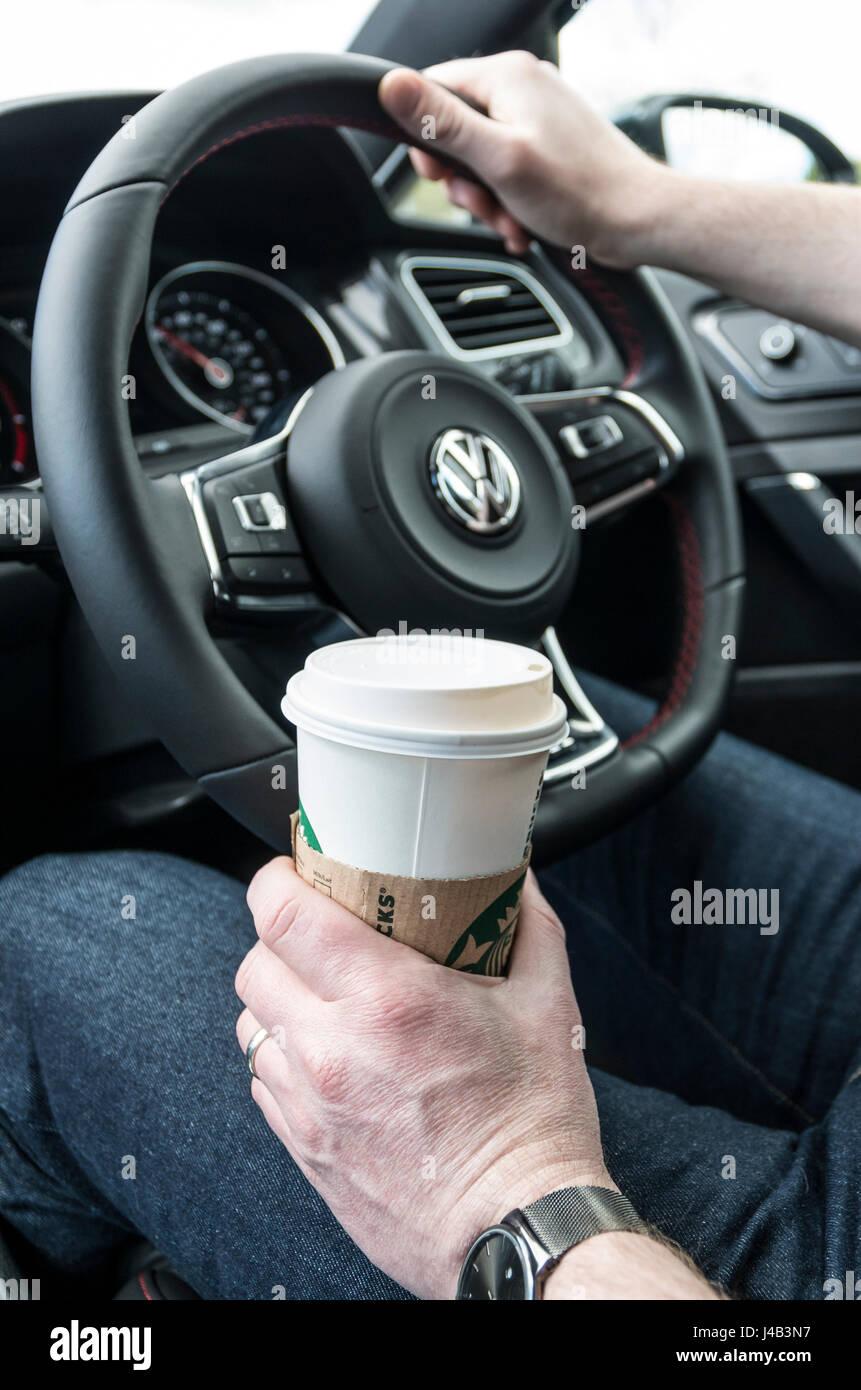 Uomo alla guida al volante di una vettura con una mano sul volante e una tazza di caffè in altri Immagini Stock