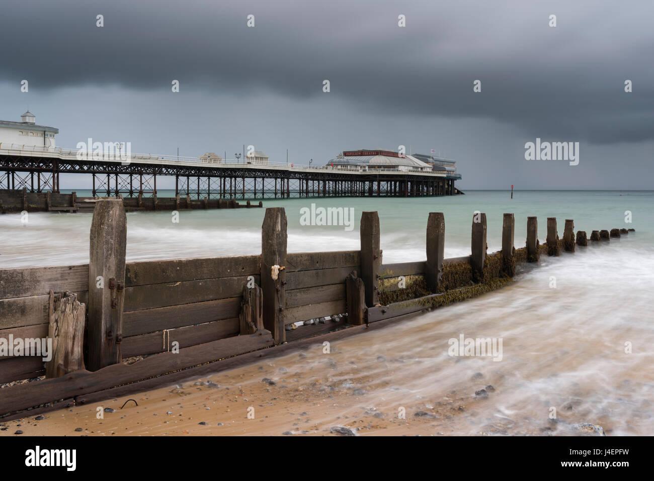 Un cielo tempestoso oltre la spiaggia e il molo a Cromer, Norfolk, Inghilterra, Regno Unito, Europa Immagini Stock