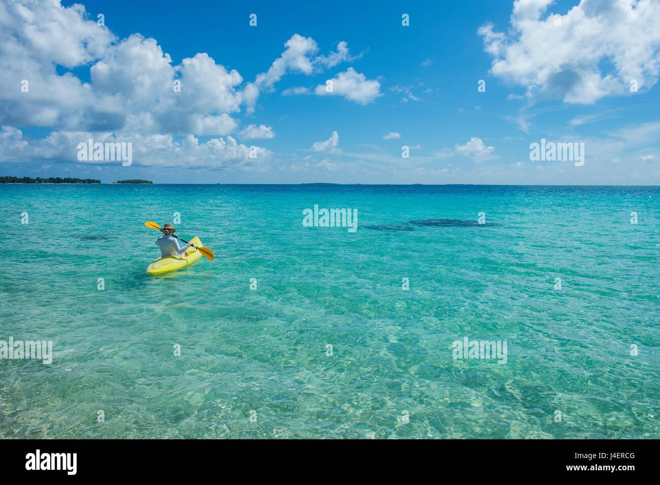 Donna kayak nelle acque turchesi di Tikehau, Tuamotus, Polinesia francese, Pacific Immagini Stock