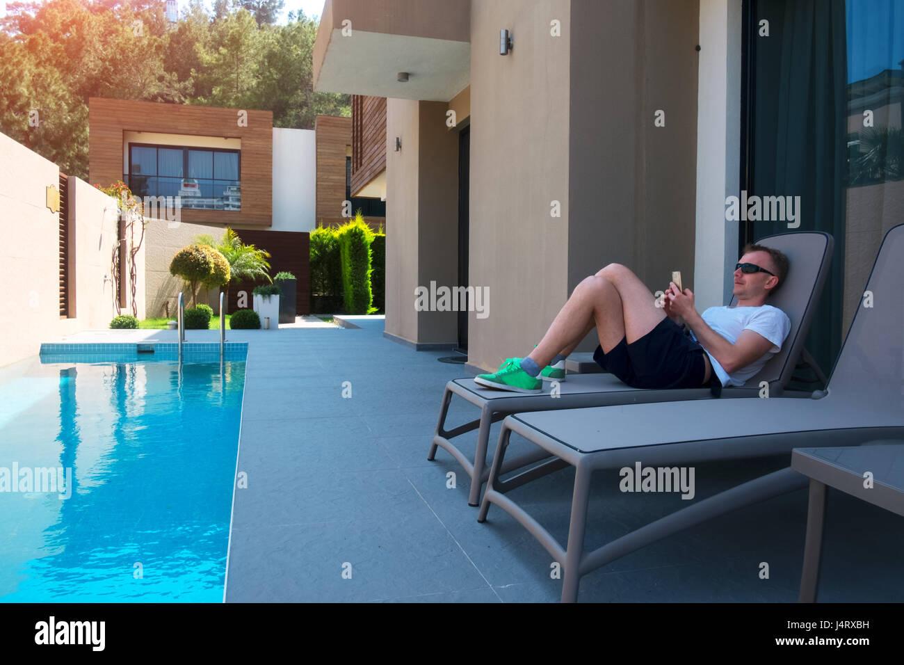 Case Moderne Con Piscina : L uomo sul rilassante lounge vicino a case moderne con piscina