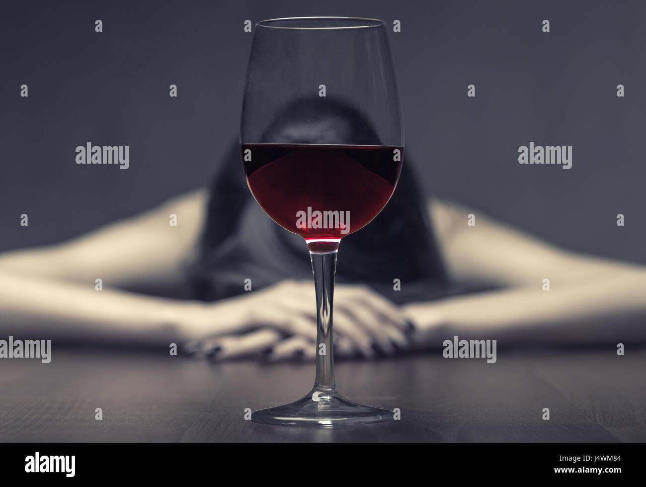 Donna in depressione, bere alcool su sfondo scuro. Focus sul vetro Immagini Stock