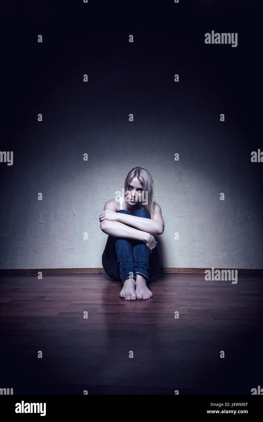 Triste giovane donna seduta da sola sul pavimento di una stanza vuota Immagini Stock