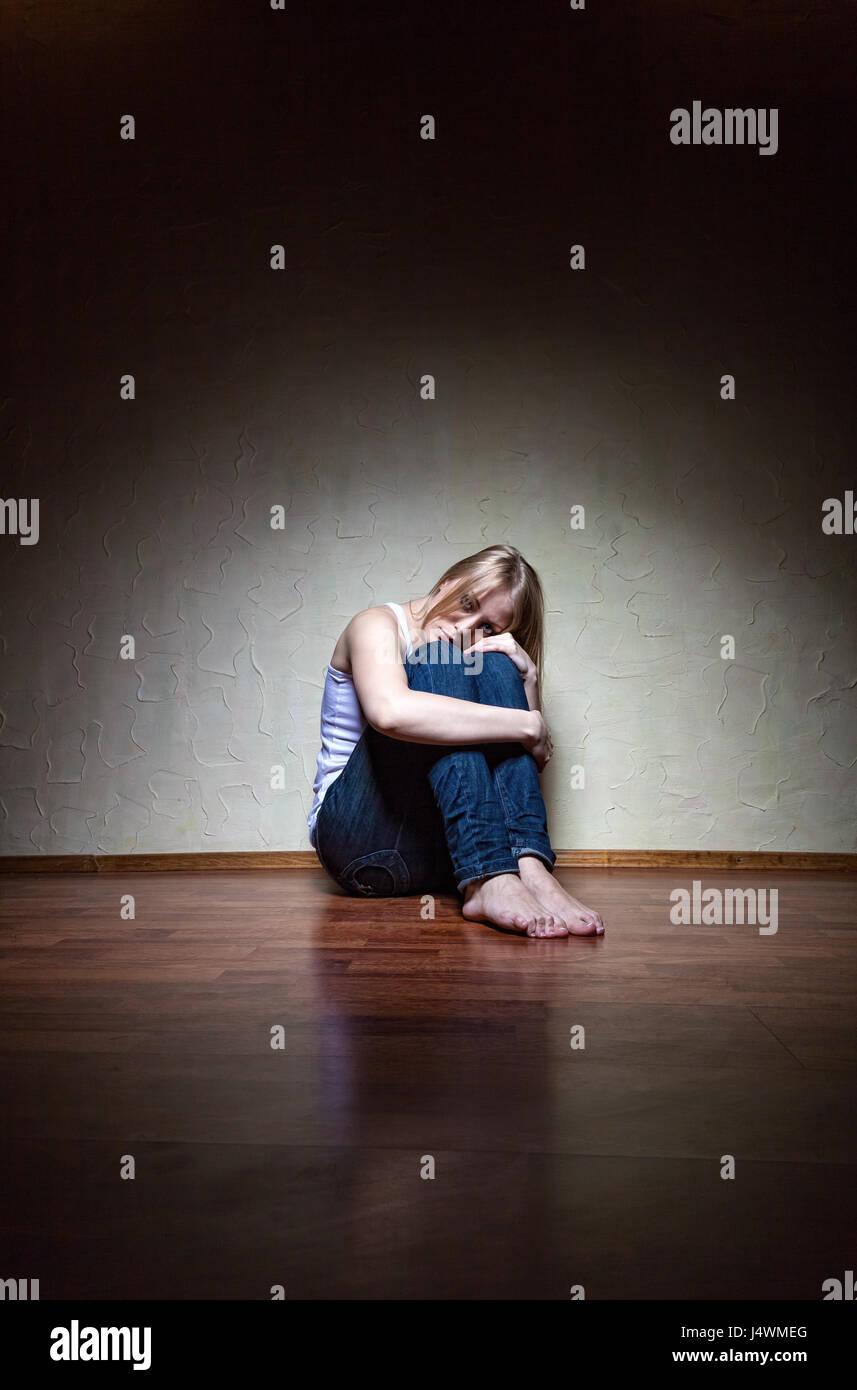 Triste donna seduta da sola in una stanza vuota Immagini Stock