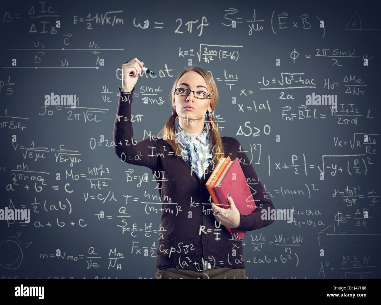 Ragazza dello studente Scrivere formule sulla parete trasparente nella sua parte anteriore Immagini Stock