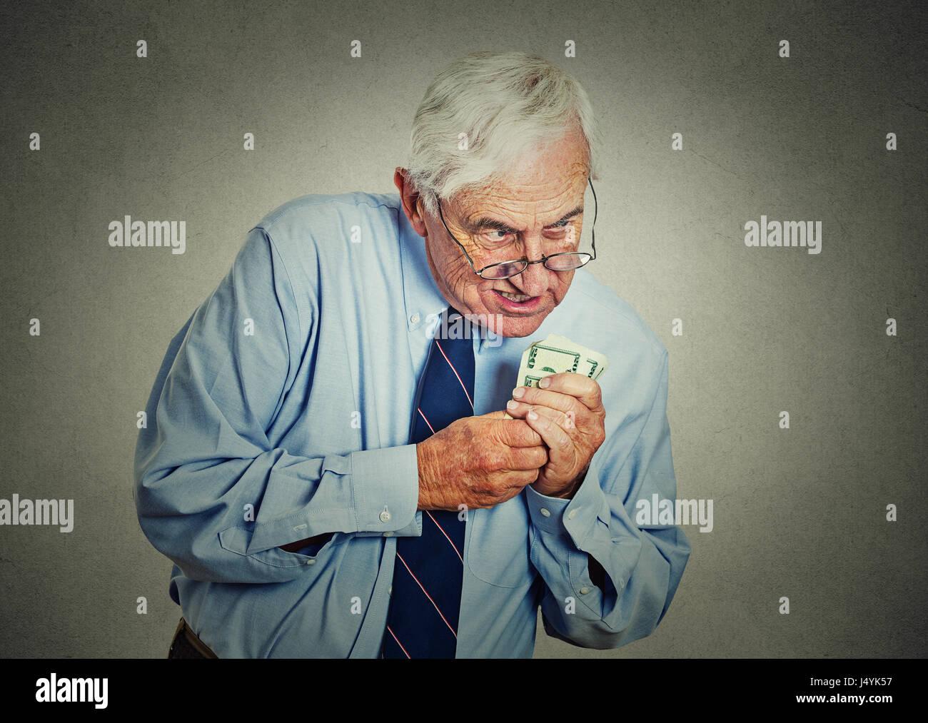 Closeup ritratto avidi di senior executive, CEO, boss, vecchio dipendente aziendale, uomo maturo, tenendo dollar Immagini Stock