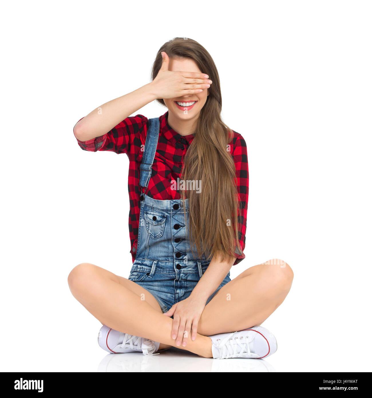 Sorridente giovane donna in rosso lumberjack t-shirt, jeans corti e bianco sneakers seduto sul pavimento con le Immagini Stock