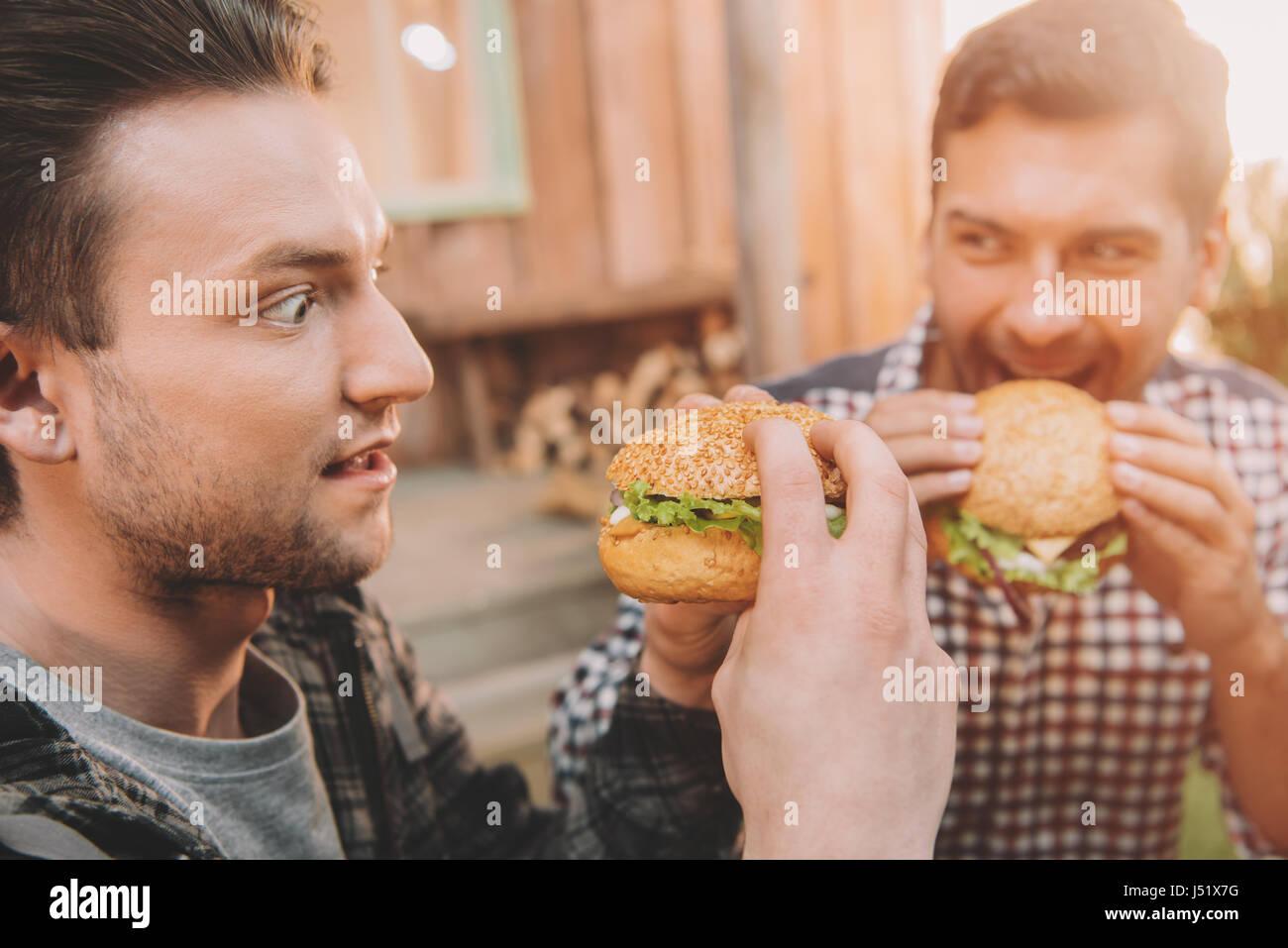 Emotional giovani uomini di mangiare hamburger gourmet all'aperto Immagini Stock