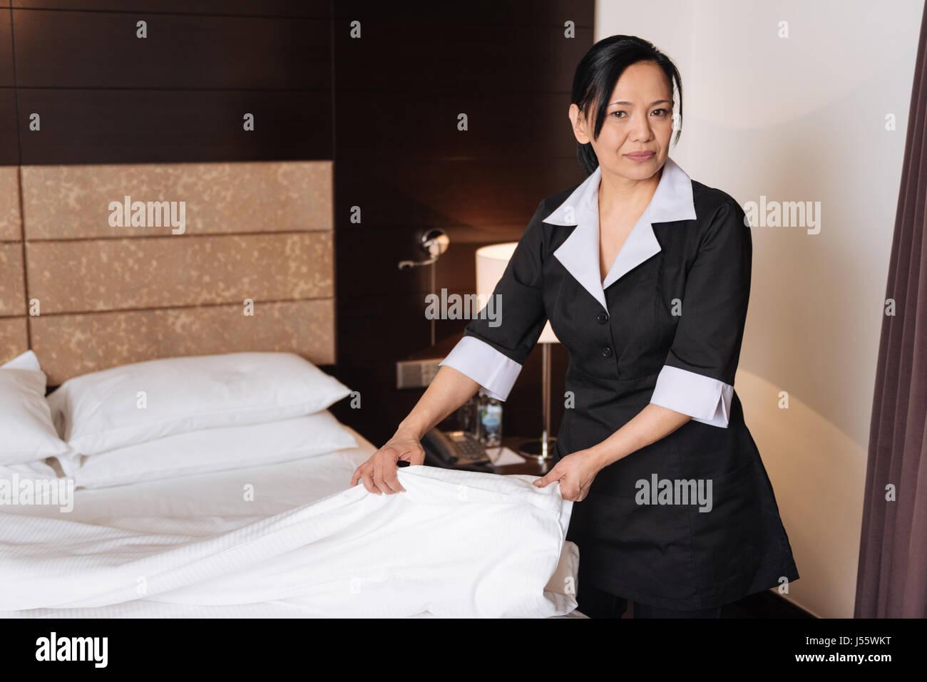 Piacevole guardando bene donna facendo il servizio in camera Immagini Stock
