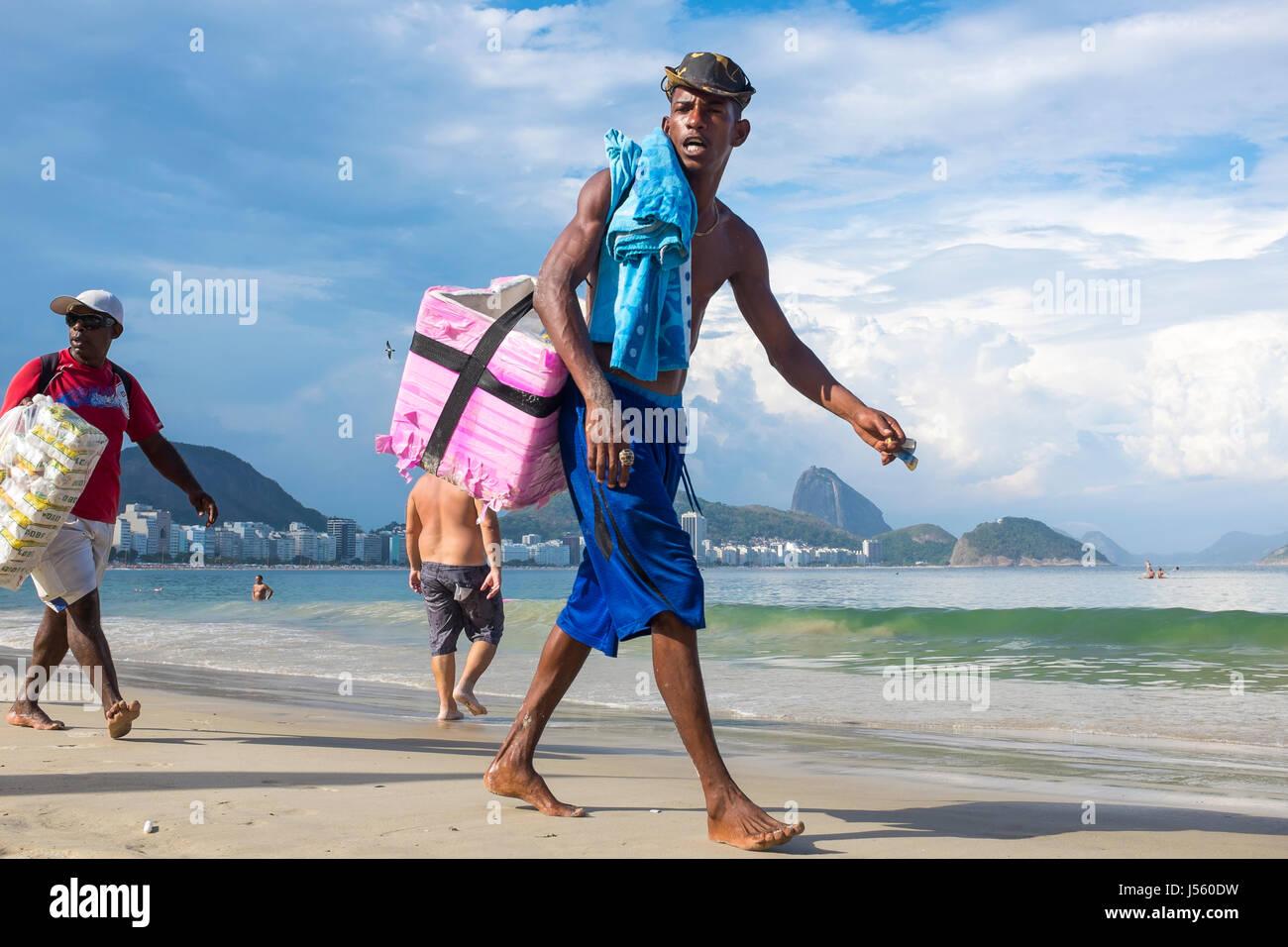 RIO DE JANEIRO - Marzo 2, 2017: Brasiliano i venditori sulla spiaggia a piedi lungo la spiaggia di Copacabana la Immagini Stock