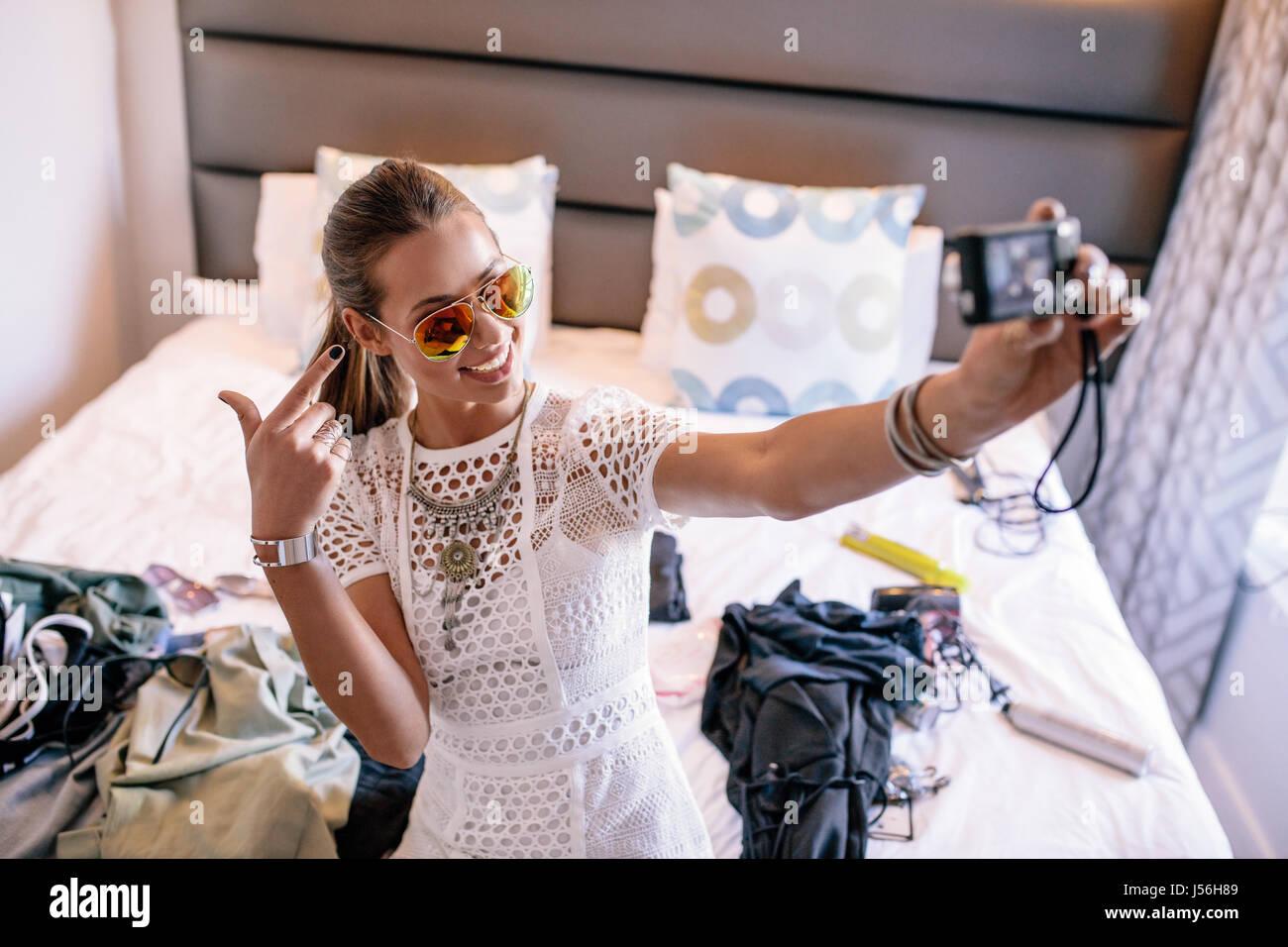 Femmina registrazione vlogger broadcast con fotocamera digitale. Donna prendendo un selfie visualizzando video moda Immagini Stock
