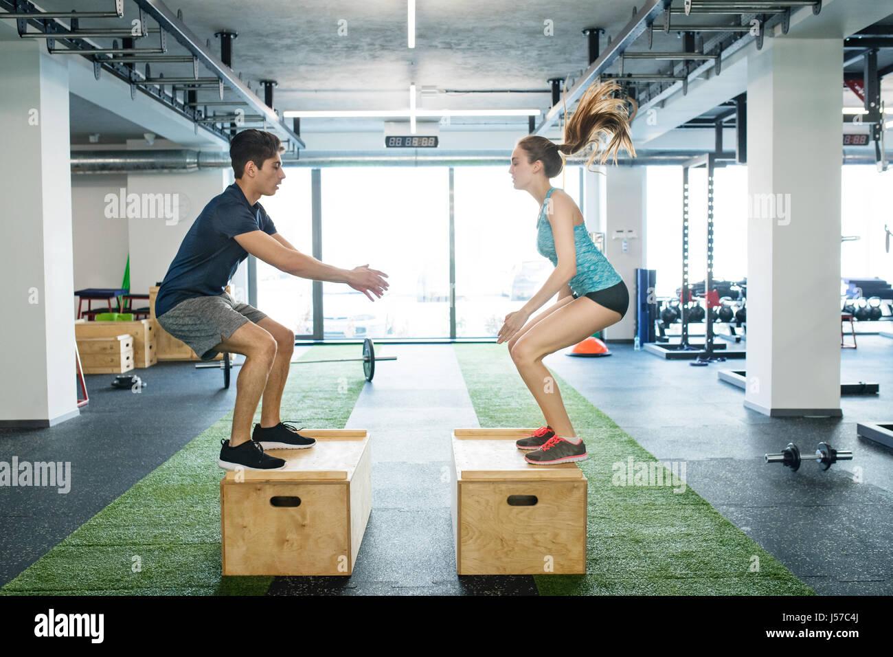 Coppia giovane e in forma esercizio in palestra, casella facendo salti. Immagini Stock